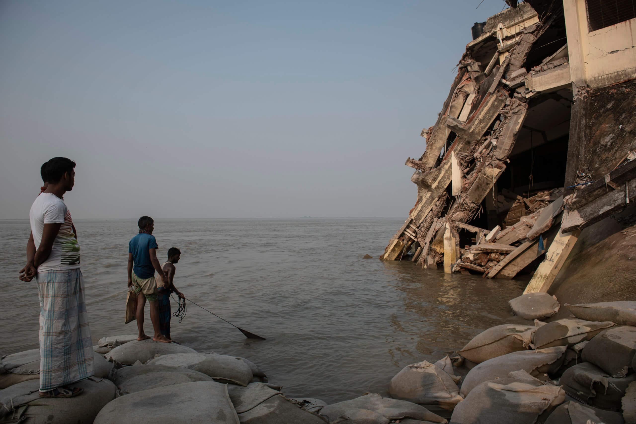 Några män fiskar i Padma-floden bredvid det nedrasade sjukhuset.