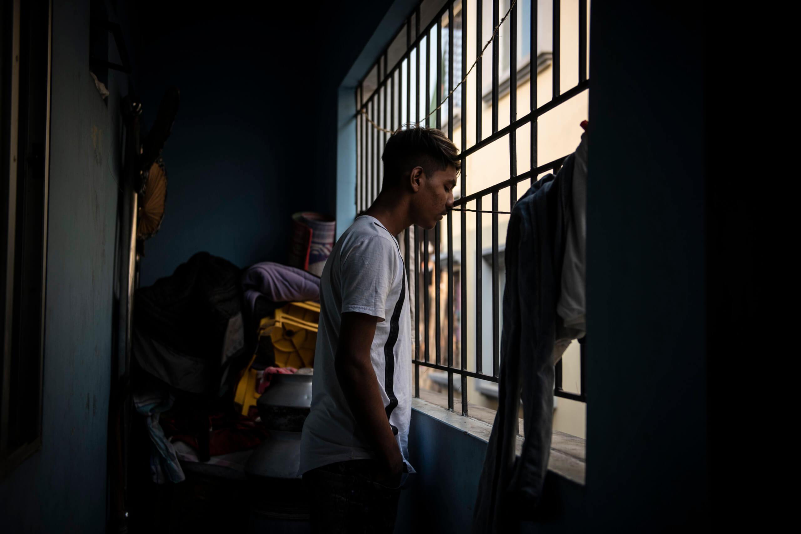 Md Sohel Sheik, 14, kollar ut genom gallret på den balkong han sover på tillsammans med sin äldre bror. Rummet deras familj delar är för litet för att de ska få plats att sova inomhus.