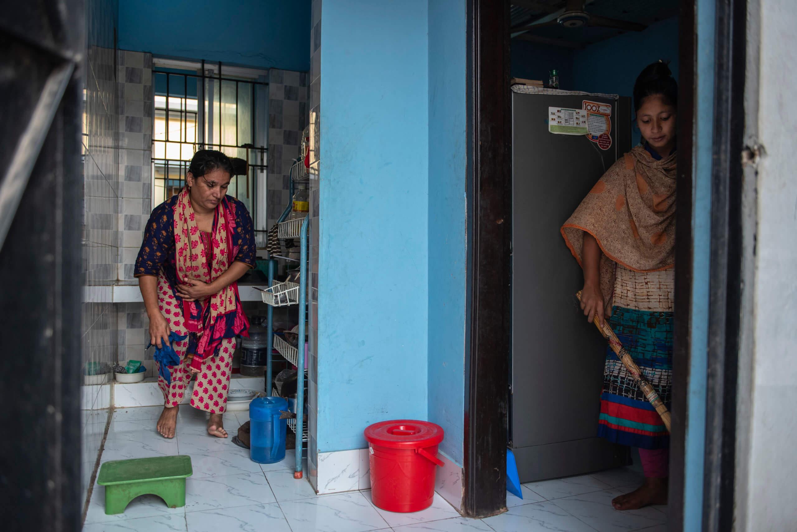 Kulsum Begum och Rupa Akter städar i ordning det gemensamma köket som de delar med andra familjer som bor husets tak.